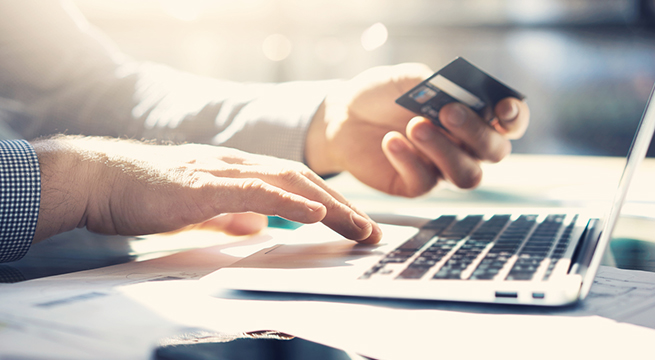 Man using laptop with credit card in hand
