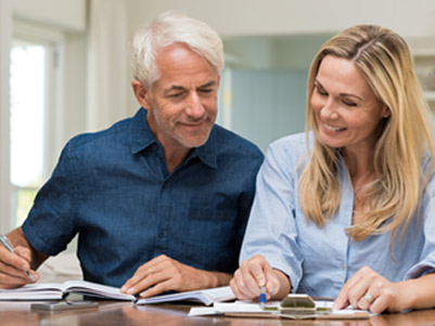 Husband and wife smiling while they look through their accounts