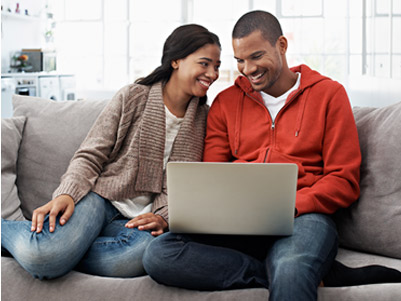 Young couple sitting together on the couch reviewing their bank statements on a laptop