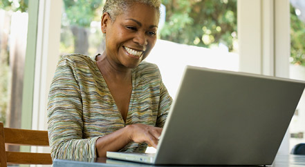 Smiling Woman using her laptop for banking.