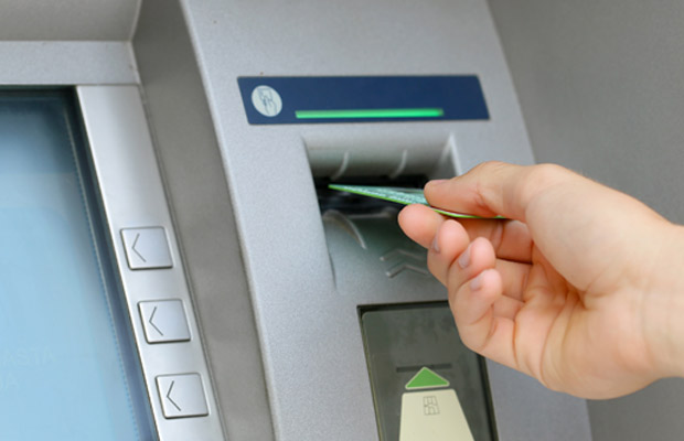 Hand putting card into ATM machine
