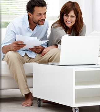 Couple viewing paperwork on laptop