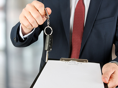 businessman offering a car key with contract
