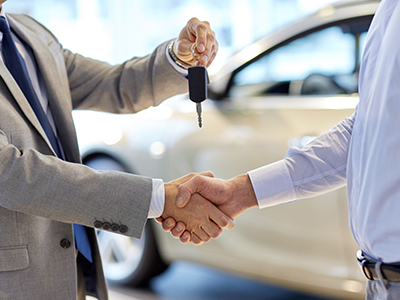 close up of handshake in auto show or salon while handing over a set of keys