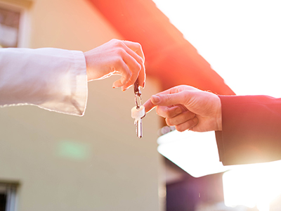 Woman handing a Man a set of keys in commercial sale