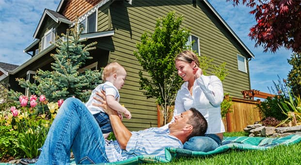 Cute couple laying on a blanket with their new baby in their front yard.