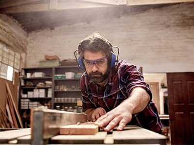 Male business owner working a table saw with safety glasses and headphones on