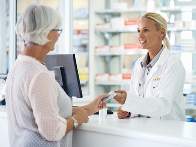 Woman Handing Credit Card to Pharmacist