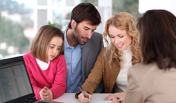 Happy family signing paperwork for their new Directions Credit Union mortgage.