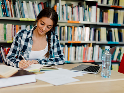 Young woman studying/writing in library setting