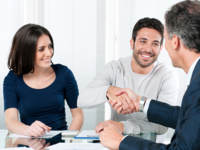 Husband and wife meeting with bank consultant; man shaking consultant's hand