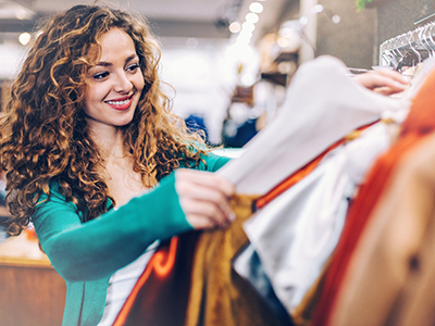 Woman looking at shirt in clothing store
