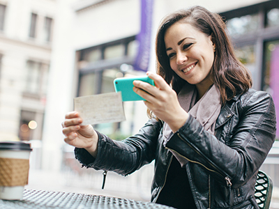 Woman smiling while depositing a check via mobile phone