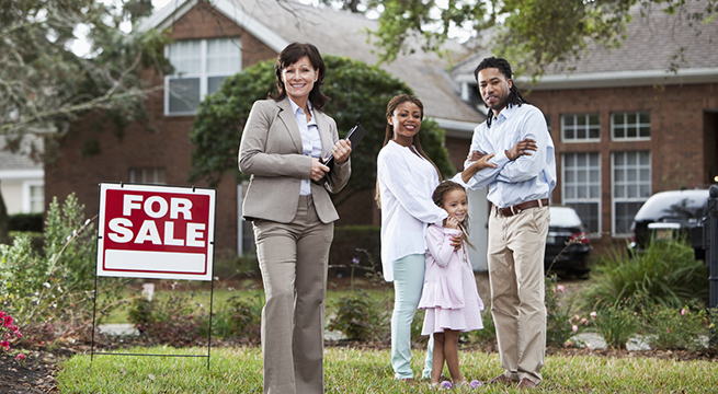 Real estate agent with family outside house