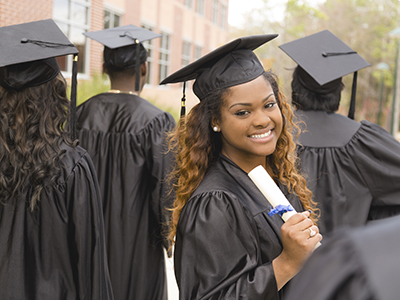Candid moment of African descent female excitedly holding her diploma after the college graduation ceremony.  Her friends around her.  School building background on campus.