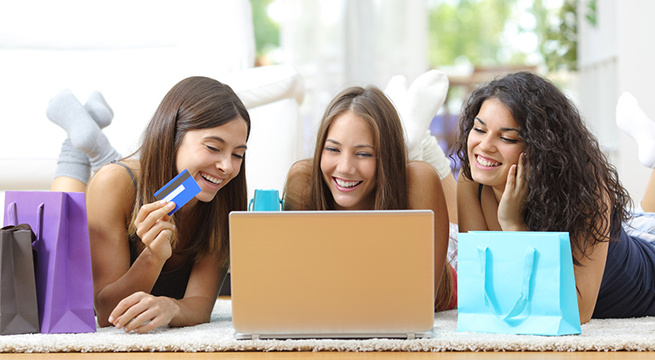 Three friends shopping online with credit card and laptop lying on the floor at home