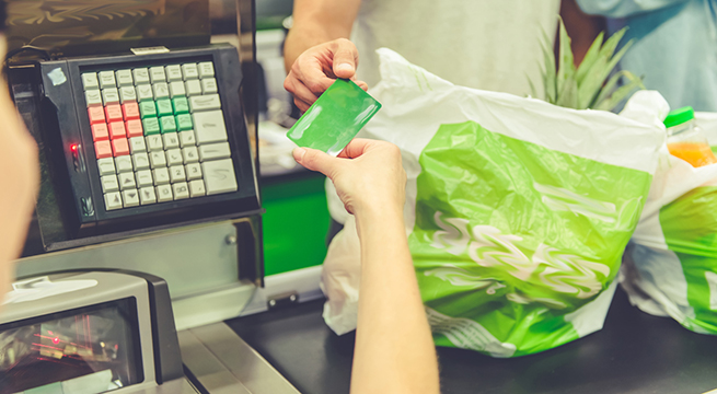 Cropped image of beautiful young couple standing near cash desk in the supermarket. Man is holding a credit card