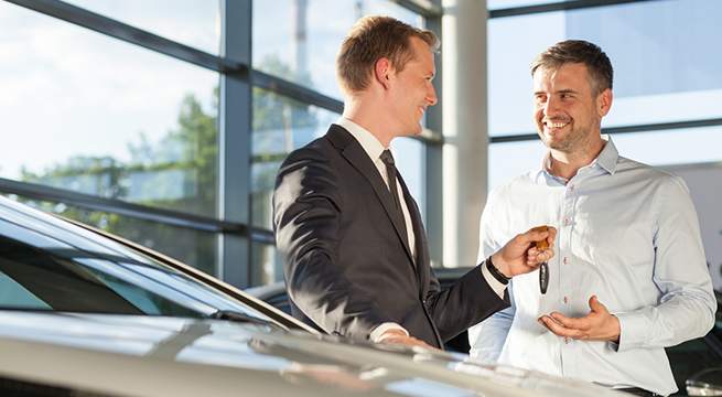 Car dealer handing keys to handsome male customer