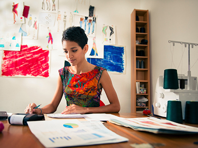 hispanic woman doing budget in fashion designer atelier