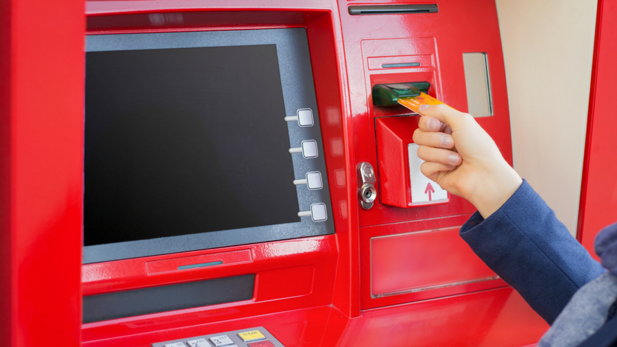Woman inserting debit card into red, ATM machine