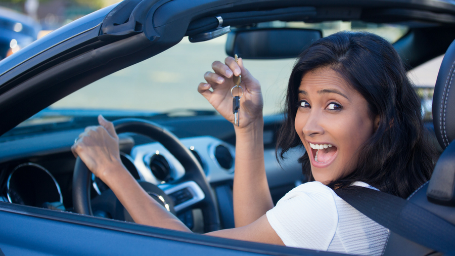 Excited, young woman holding up keys while sitting in her new convertible vehicle