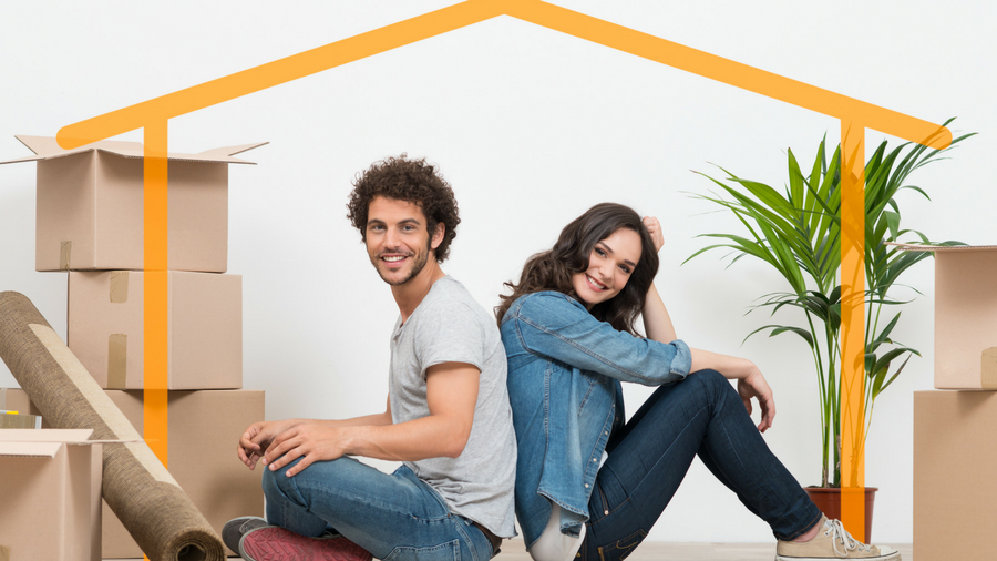 Smiling couple sitting on the floor back to back with a outline of a house over them, moving boxes around them