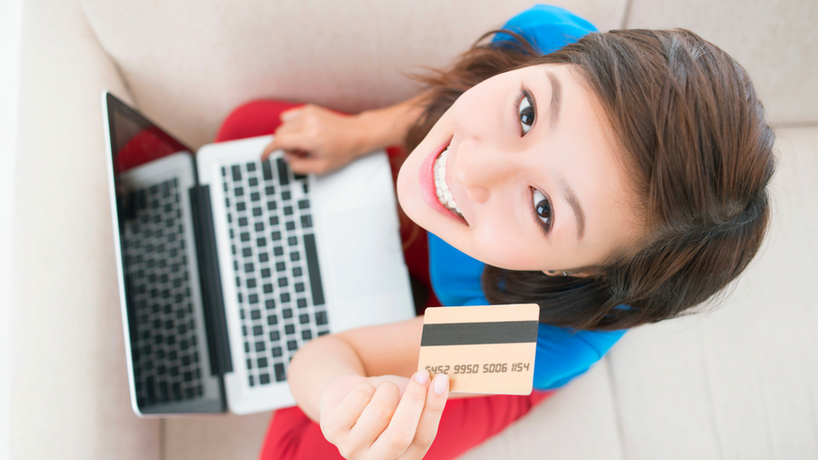 Young girl looking up to the camera holding a debit card with laptop on her lap