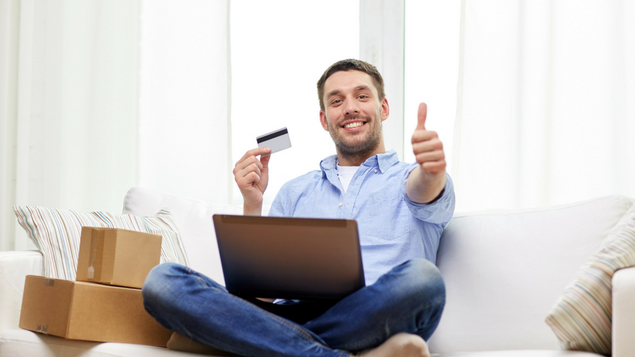 Young, smiling, man sitting cross legged on couch with laptop on lap holding debit card in one hand and giving a thumbs up with the other: 2 boxes stacked placed next to him
