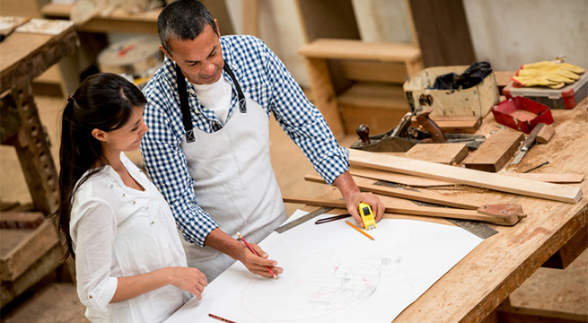 Carpenter reviewing plans with new customer