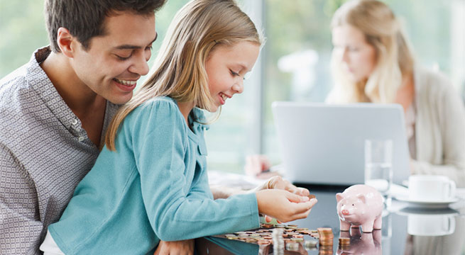 Child counting money sitting on father's lap; mother on laptop in background