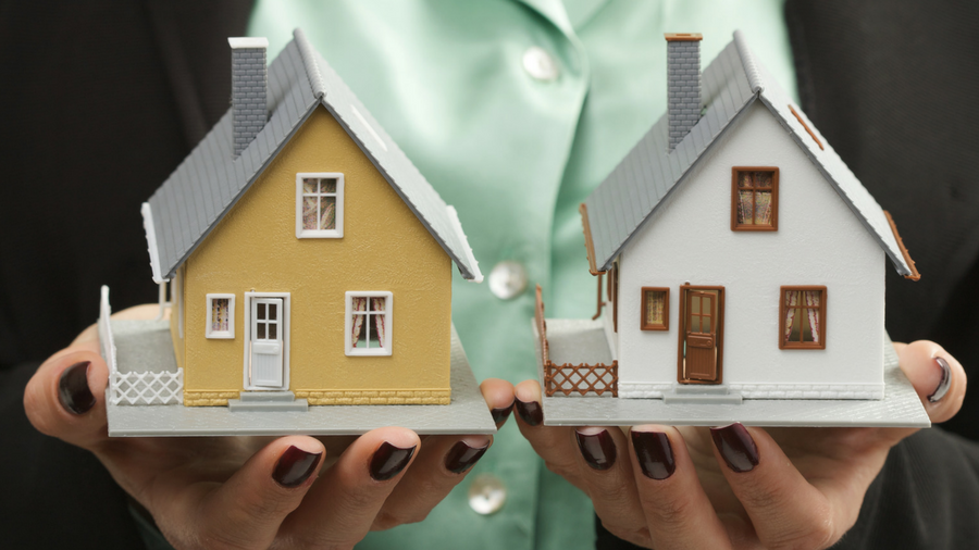 Business woman holding two miniature model homes in her hands