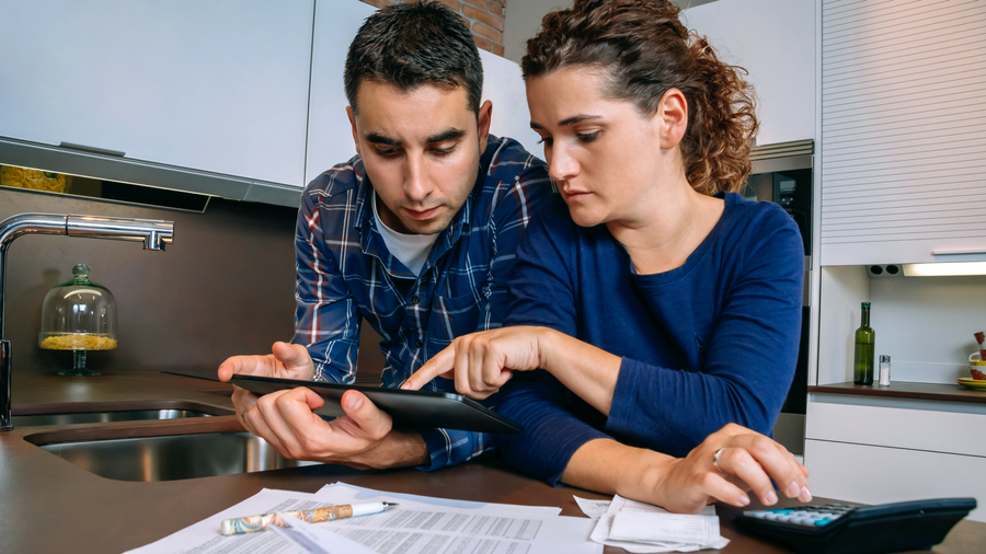Couple going over bank statements and receipts in their kitchen utilizing a tablet and calculator