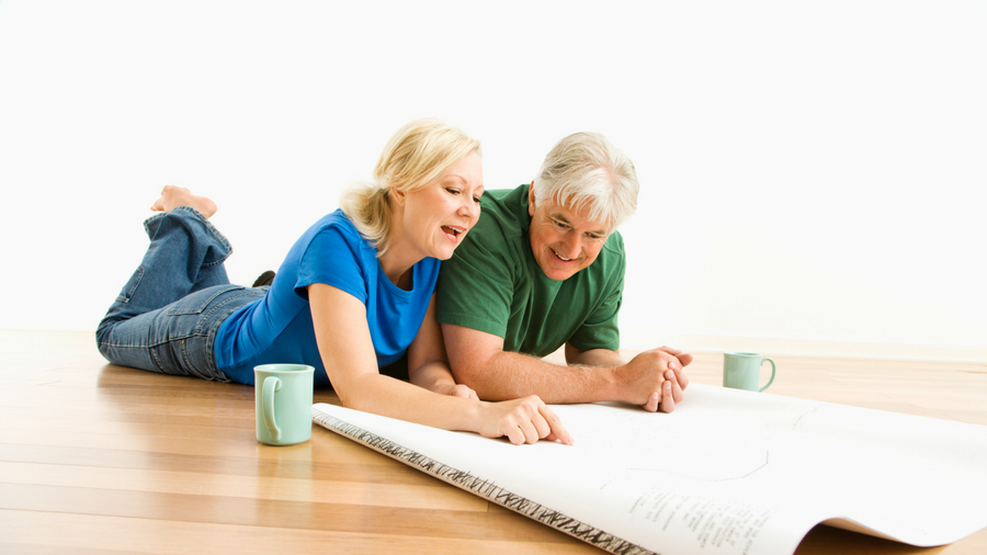 Older couple laying on the floor, coffee cups next to each while reviewing home improvement plans