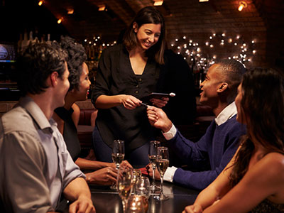 Man out to dinner with friends pays with iDirect prepaid card