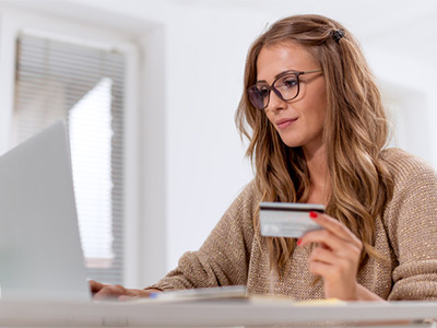 Young woman with credit card on a computer and smiling.