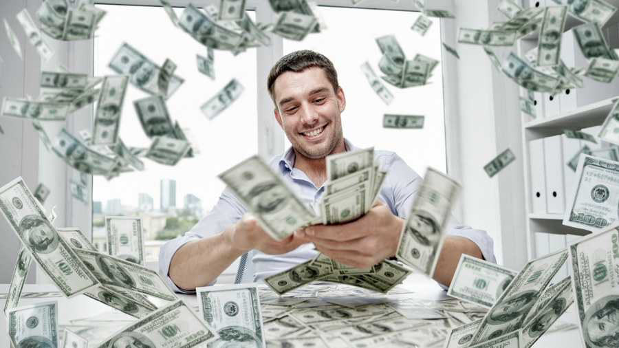 Man smiling while counting out one hundred dollar bills: bills flying all around him and in front of him