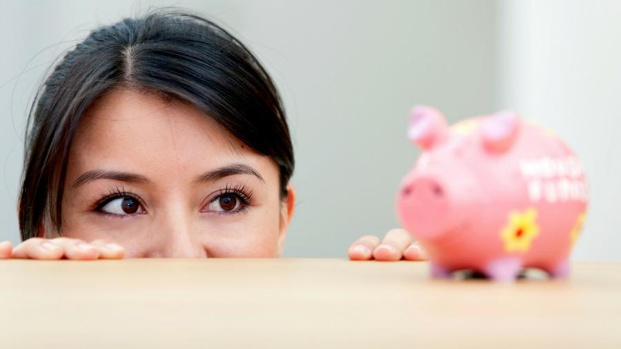 Young woman peeking up at a piggy bank