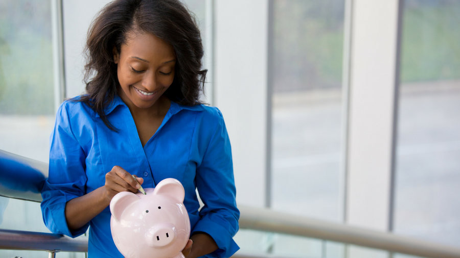 Woman looking down and putting money in a piggy bank while holding it