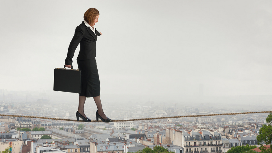Business woman holding brief case while balancing and walking on a tightrope above the city