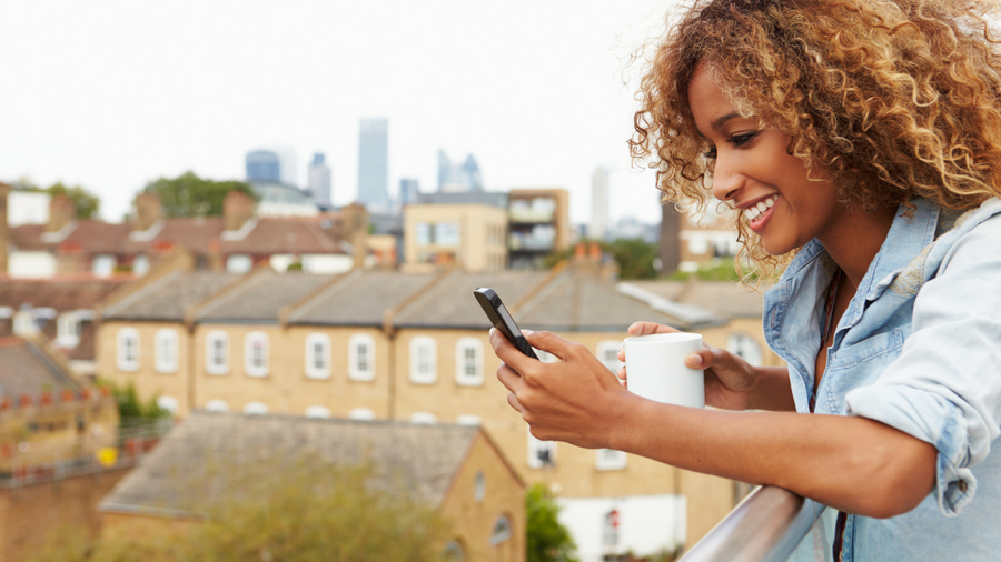 Woman scrolling through phone while on balcony holding cup of coffee