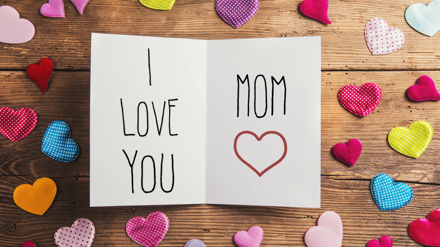 "Open greeting card that reads ""I Love You Mom"" with a red, outlined heart laying on a table surrounded by different colored fabric hearts"