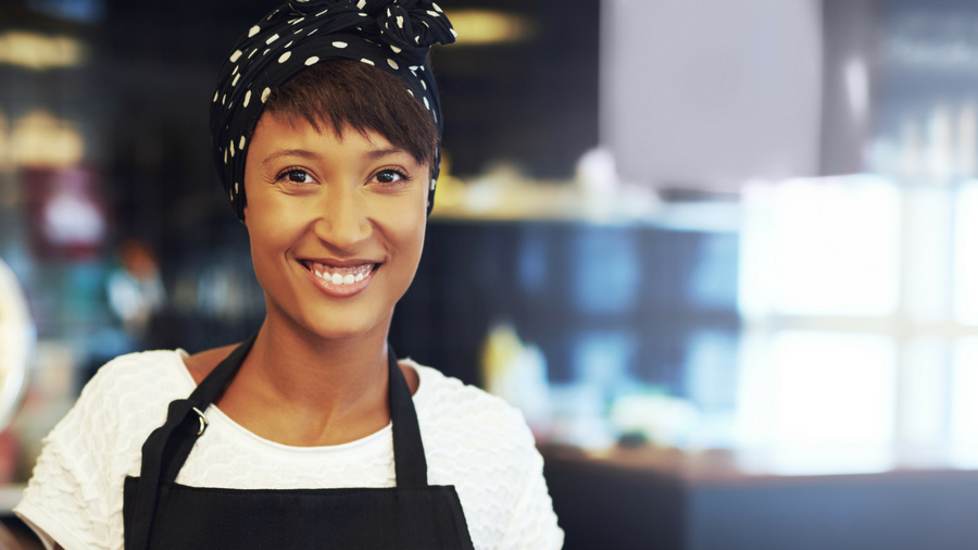 Young new, small business owner, smiling with black apron on