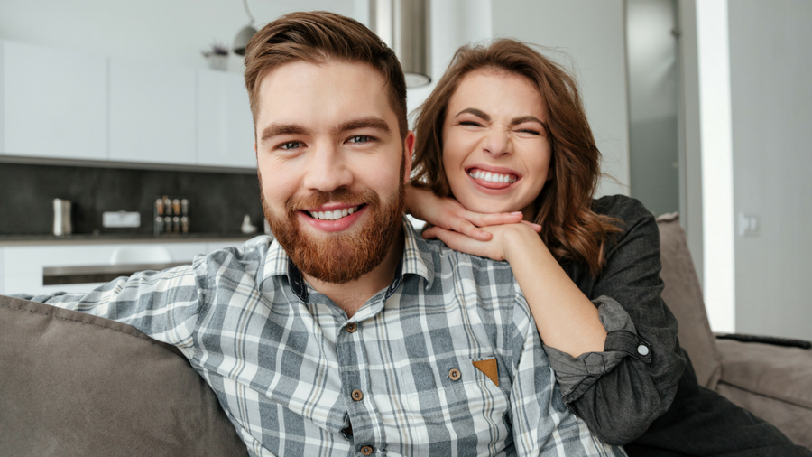 Young couple sitting on couch, woman making silly, happy face over husband's shoulder, man smiling