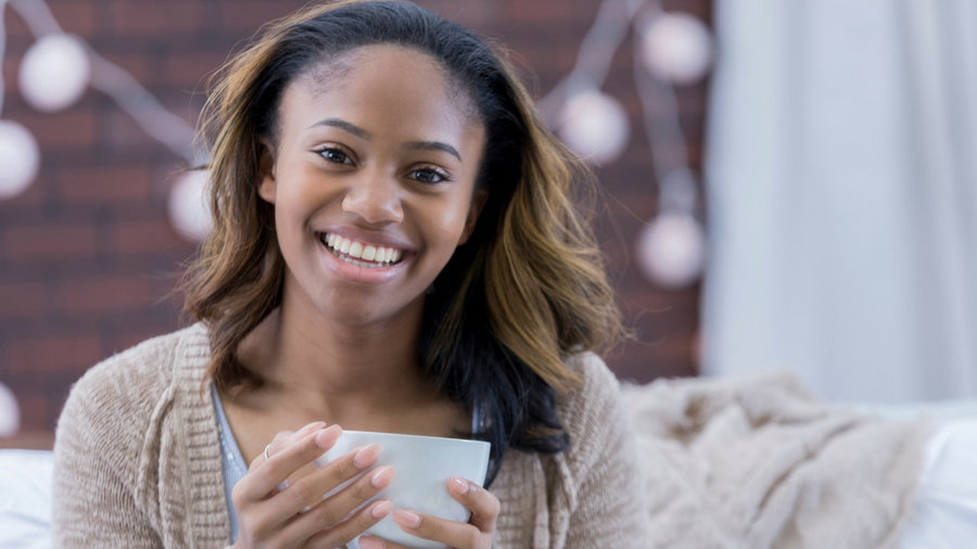 Young woman, college student, holding coffee cup, smiling into the camera