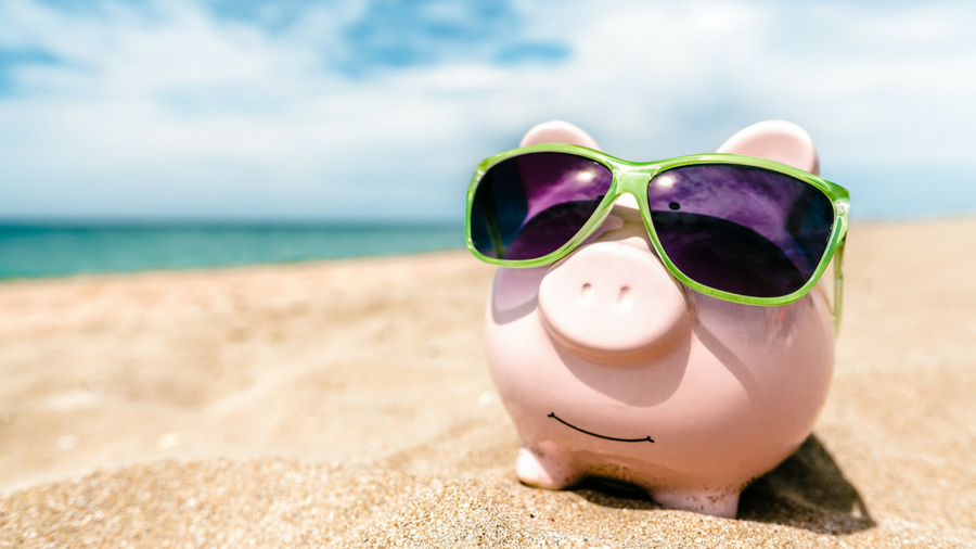 Piggy bank with sunglasses on in the sand on a beach