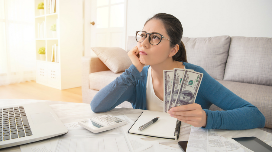Young woman holding money in hand while contemplating her bills